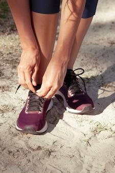 Close de uma mulher amarrando o cadarço do tênis enquanto caminha ou faz exercícios ao ar livre em um parque