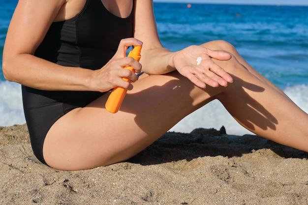 Close de uma mulher aplicando protetor solar, areia, praia, mar azul