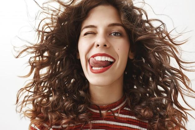 Close de uma mulher atraente despreocupada com cabelos cacheados sorrindo