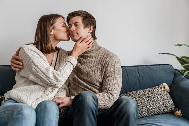Close de uma mulher beijando o marido