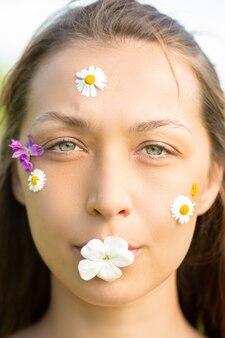 Close de uma mulher bonita com flores silvestres na testa e bochechas