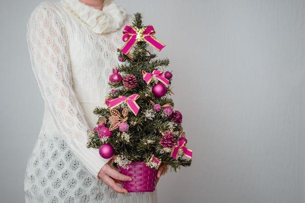 Close de uma mulher branca segurando uma pequena árvore de natal em um vaso com enfeites roxos