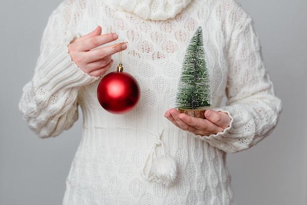 Close de uma mulher branca segurando uma pequena árvore de natal em uma e uma bola vermelha na outra