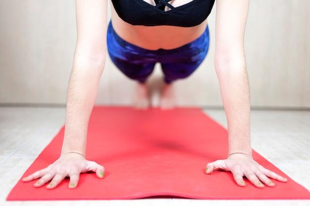 Close de uma mulher caucasiana, fazendo algumas flexões em um tapete de ioga dentro de casa