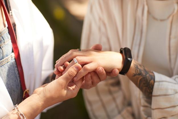 Close de uma mulher colocando o anel no dedo da namorada, fazendo-lhe uma proposta