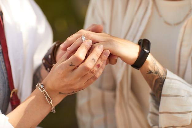 Close de uma mulher colocando um anel no dedo da namorada, noivos