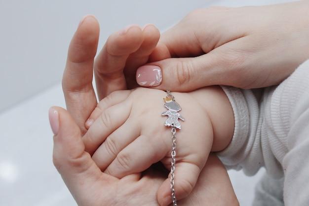 Close de uma mulher colocando uma linda pulseira na mão do bebê