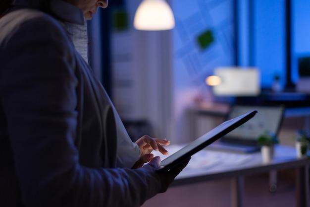 Close de uma mulher com as mãos digitando em um tablet, verificando os gráficos financeiros em pé no escritório de start-up tarde da noite