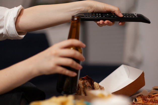 Close de uma mulher com as mãos mudando de canal usando o controle remoto assistindo a um filme de comédia de entretenimento