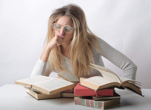 Close de uma mulher com cabelo bagunçado lendo vários livros na frente dela
