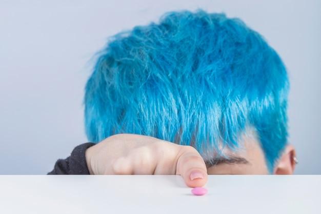 Close de uma mulher com cabelo tingido azul, apontando o dedo em direção a pílula rosa na mesa