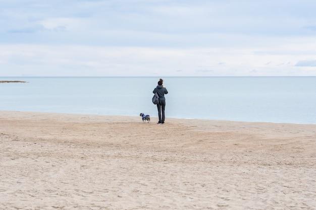 Close de uma mulher com seu cachorro em uma praia e observando a bela vista