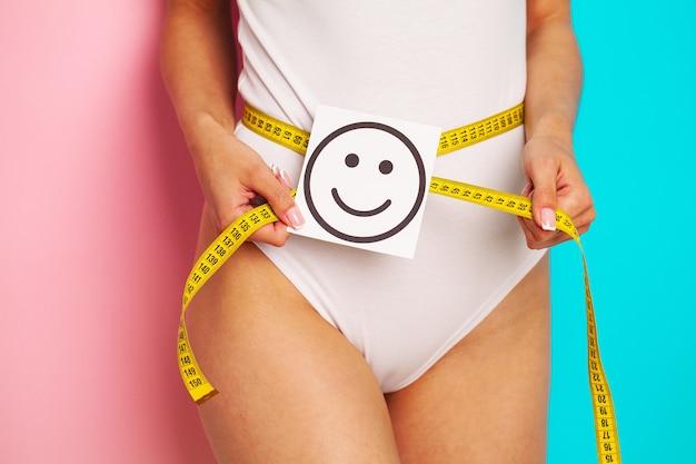 Close de uma mulher com uma figura esguia demonstra o resultado segurando um cartão perto de sua barriga com um sorriso sorridente e fita métrica amarela