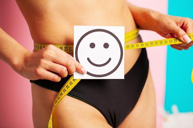 Close de uma mulher com uma figura esguia mostra o resultado segurando um cartão perto de sua barriga com um sorriso e uma fita métrica amarela.