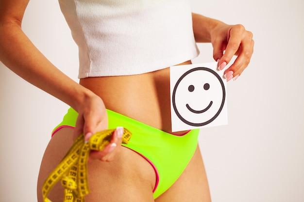 Close de uma mulher com uma figura esguia mostra o resultado segurando um cartão perto de sua barriga com um sorriso sorridente e fita métrica amarela