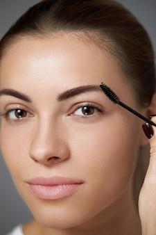 Close de uma mulher com uma sobrancelha em formato perfeito, cílios longos e maquiagem profissional