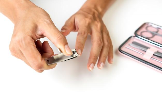 Close de uma mulher cortando unhas, usando cortador de unhas com conjunto de instrumentos de manicure e ferramentas no caso rosa, conceito de cuidados de saúde