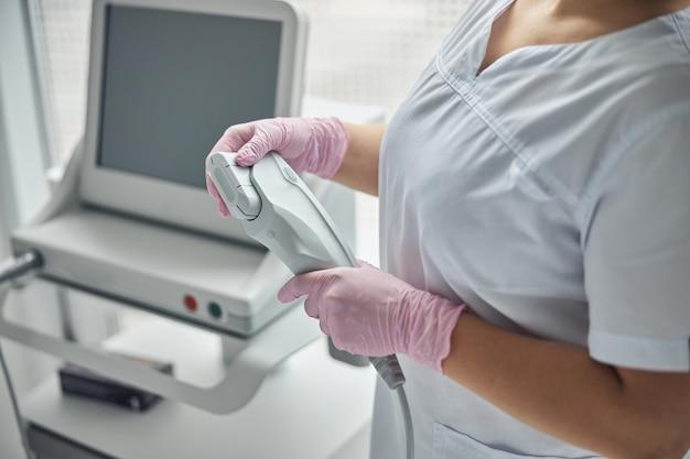 Close de uma mulher cosmetologista com as mãos em luvas estéreis segurando um dispositivo de depilação a laser e rejuvenescimento da pele