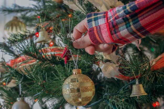 Close de uma mulher decorando uma árvore de natal com bolas brilhantes