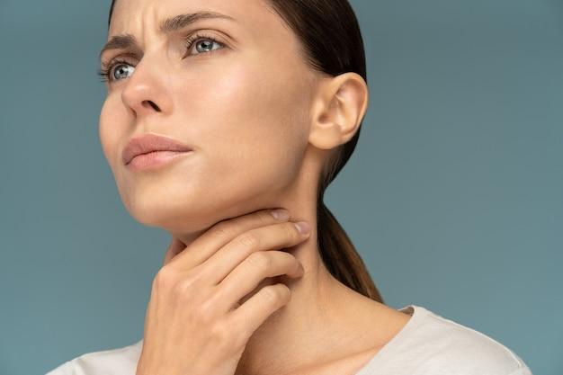 Close de uma mulher doente, com dor de garganta, enjoada, segurando a mão em seu pescoço