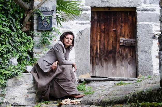 Close de uma mulher elegante sentada perto de uma velha porta de madeira