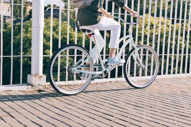 Close de uma mulher em uma jaqueta e calça jeans, andar de bicicleta da cidade