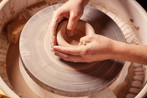 Close de uma mulher esculpindo lindamente um vaso de argila marrom em uma roda de oleiro