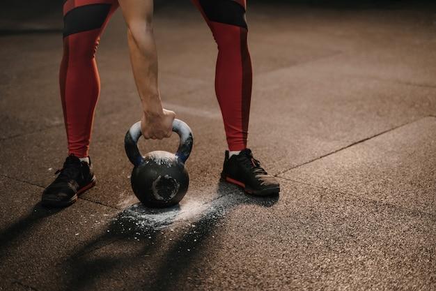 Close de uma mulher esportiva segurando um kettlebell enquanto treina