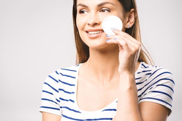 Close de uma mulher feliz limpando o rosto com almofadas de algodão