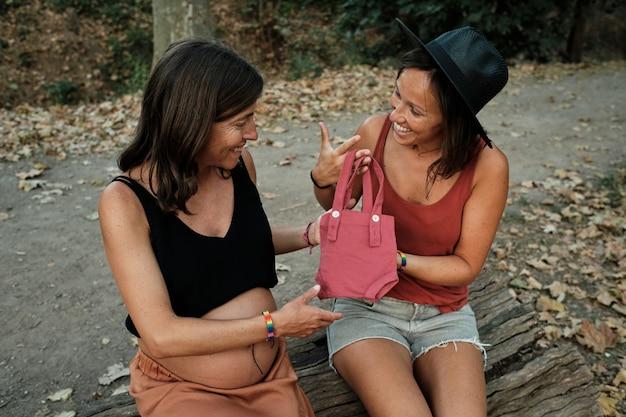Close de uma mulher grávida e seu parceiro falando sobre uma bolsa rosa em um parque