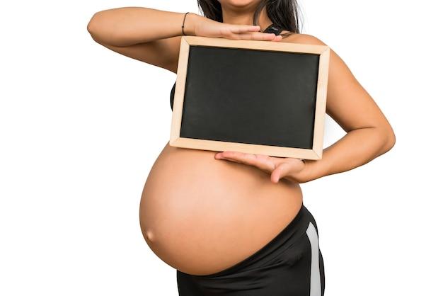 Close de uma mulher grávida segurando e mostrando algo no quadro-negro