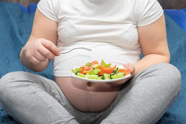 Close de uma mulher grávida segurando um prato de salada de legumes fatiada. estilo de vida saudável e conceito de nutrição durante a gravidez