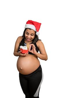 Close de uma mulher grávida segurando uma caixa de presente de natal