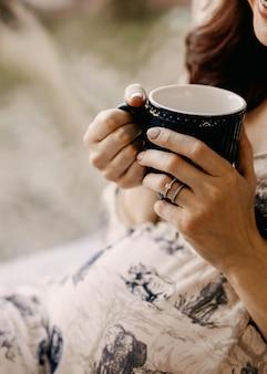 Close de uma mulher grávida segurando uma xícara de café