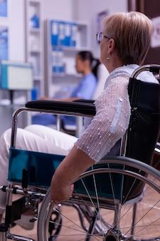 Close de uma mulher idosa deficiente, paralisada e com deficiência em uma cadeira de rodas, chegando sozinha à clínica médica, esperando o exame médico no corredor do hospital