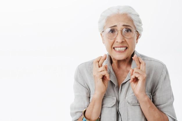 Close de uma mulher idosa preocupada e nervosa usando óculos, dedos cruzados e orando