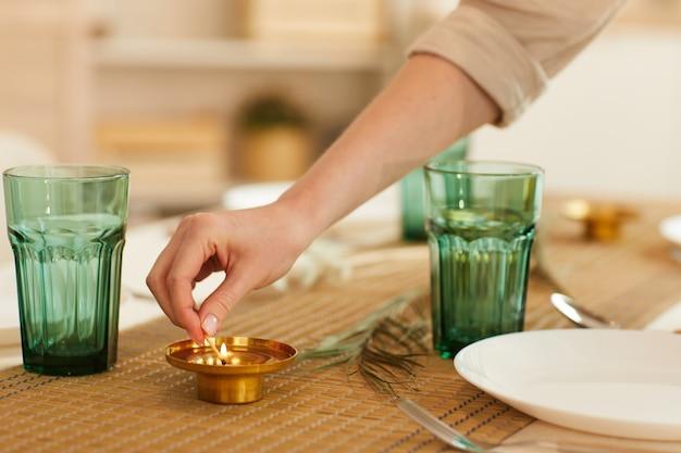 Close de uma mulher irreconhecível acendendo uma vela enquanto servia a mesa para os convidados