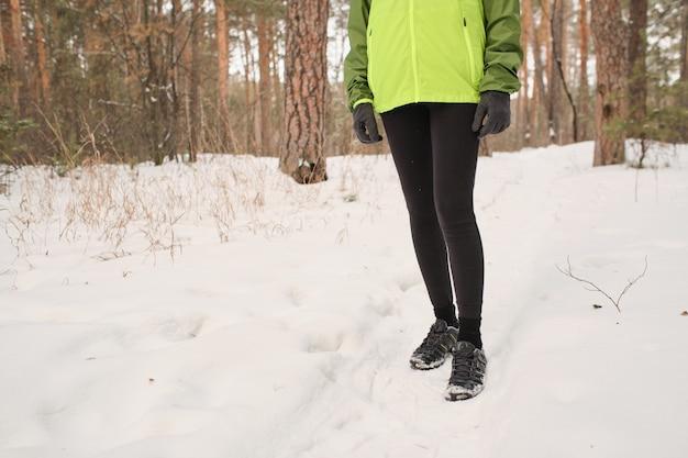 Close de uma mulher irreconhecível com tênis, caminhando na floresta de inverno