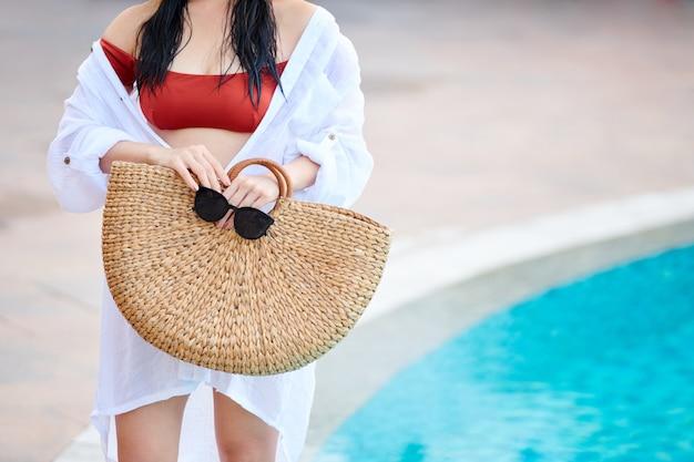 Close de uma mulher irreconhecível com uma camisa branca de praia em pé, um saco de palha e óculos de sol à beira da piscina