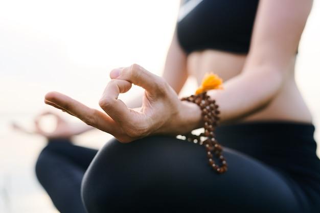 Close de uma mulher irreconhecível concentrada em pensamentos usando contas de mala no pulso e meditando com as mãos em mudra