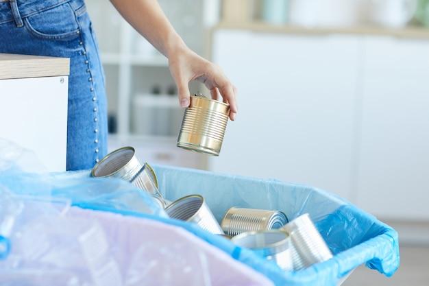 Close de uma mulher jogando as latas no lixo em casa