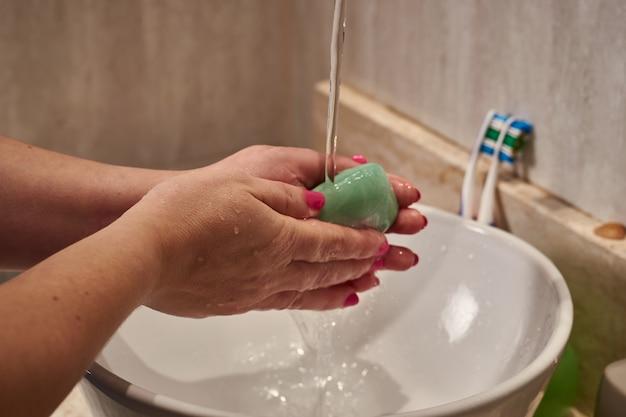 Close de uma mulher lavando as mãos com uma barra de sabão sob as luzes em um banheiro