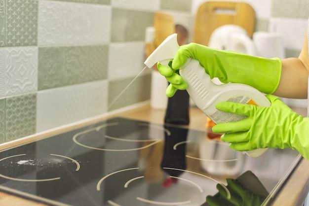 Close de uma mulher limpando a superfície de vitrocerâmica de cozinha moderna com esponja e detergente