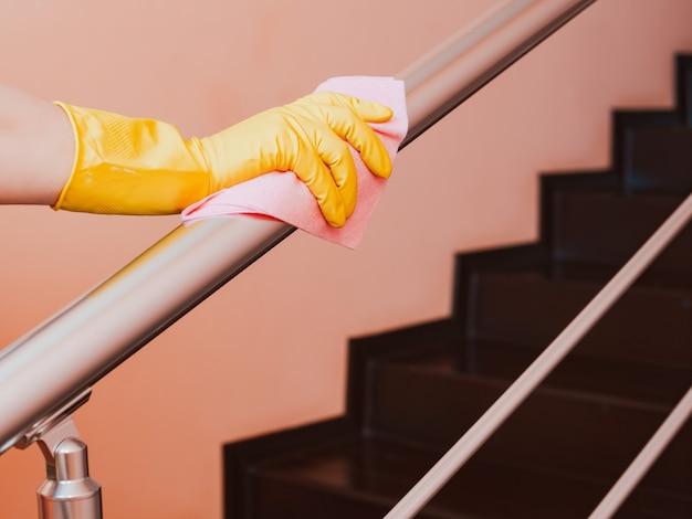 Close de uma mulher limpando o corrimão da escada