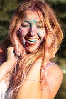 Close de uma mulher loira feliz coberta com tinta colorida holi, mostrando a língua