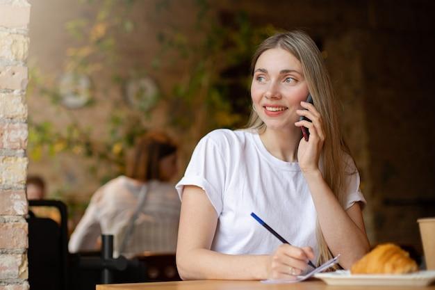 Close de uma mulher loira feliz em uma camiseta branca olha pela janela e fala ao telefone, escrevendo no papel enquanto trabalhava no café à mesa com um croissant e uma bebida