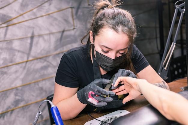 Close de uma mulher manicure remove verniz gel das unhas da cliente usando uma máquina de manicure
