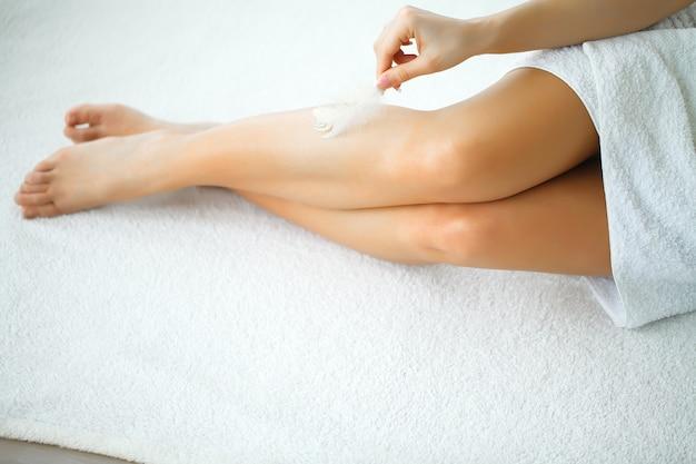 Close de uma mulher mostrando as pernas lisas perfeitas
