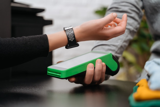 Close de uma mulher pagando a compra por meio de smartwatch usando tecnologia nfc em uma loja de roupas