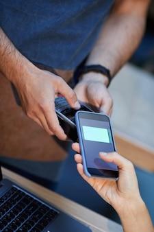 Close de uma mulher pagando online com seu celular, sentada em um café
